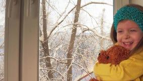 Juegos del bebé que se sientan en el alféizar en el fondo de árboles nevados almacen de metraje de vídeo