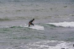 Juegos del hombre de la persona que practica surf con las ondas Foto de archivo