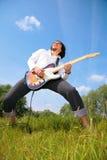 Juegos del hombre joven en la guitarra en hierba Fotografía de archivo
