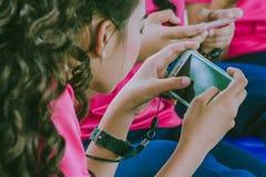 Juegos del juego de los estudiantes con los teléfonos móviles fotografía de archivo libre de regalías