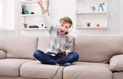 Juegos del juego del adolescente en el sofá en casa Imagenes de archivo