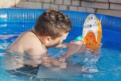 Juegos del muchacho con el barco en la piscina Fotografía de archivo