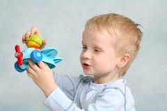 Juegos del muchacho con el plano del juguete Imagen de archivo libre de regalías