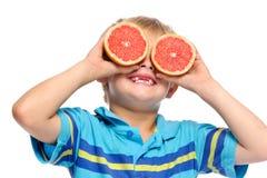 Juegos del muchacho con la fruta fresca Foto de archivo libre de regalías