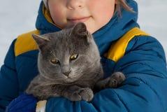 Juegos del muchacho con un gato al aire libre Fotografía de archivo