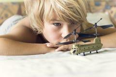 Juegos del muchacho con un helicóptero Fotografía de archivo