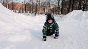 Juegos del muchacho en la nieve Arrastres a lo largo de una trayectoria nevosa entre las nieves acumulada por la ventisca en el p almacen de metraje de vídeo