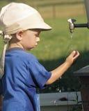 Juegos del niño pequeño con agua (1) Foto de archivo libre de regalías