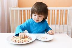 Juegos del niño pequeño con arroz y habas de cáscara Fotos de archivo libres de regalías