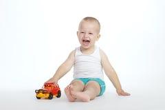 Juegos del niño pequeño con el coche del juguete Imagen de archivo