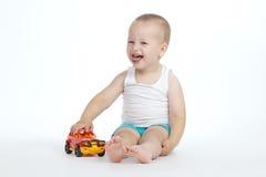 Juegos del niño pequeño con el coche del juguete Fotografía de archivo