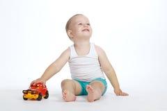 Juegos del niño pequeño con el coche del juguete Foto de archivo