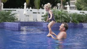 Juegos del papá con su pequeña hija en la piscina al aire libre almacen de metraje de vídeo