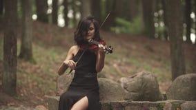 Juegos elegantes del violinista con la inspiración Muchacha en el vestido que toca el violín en bosque metrajes