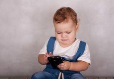 Juegos europeos del bebé con un smartphone fotos de archivo