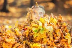 Juegos felices de la niña con las hojas de otoño foto de archivo