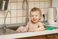 Juegos felices del muchacho en el fregadero de cocina Imagen de archivo