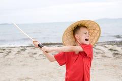 Juegos gritadores del muchacho con la espada del samurai Imagen de archivo libre de regalías