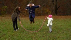 Juegos jovenes de la madre con los niños en cuerda de salto hermosa de la muchacha del bosque del otoño la pequeña La familia es  metrajes