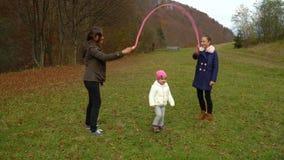Juegos jovenes de la madre con los niños en cuerda de salto hermosa de la muchacha del bosque del otoño la pequeña La familia es  almacen de video
