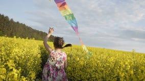 Juegos lindos de la muchacha con la cometa colorida