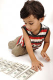 Juegos lindos del muchacho con el dinero Fotografía de archivo libre de regalías