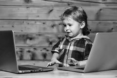 Juegos lindos del muchacho en los ordenadores fotos de archivo libres de regalías