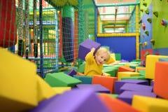 Juegos lindos del niño pequeño con los cubos suaves en la piscina seca en centro del juego Niño que juega en patio interior en ho foto de archivo libre de regalías