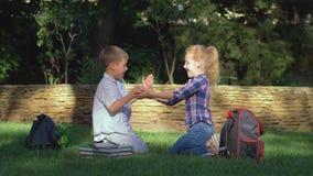 Juegos, muchacha educativa del escolar y muchacho jugando al juego que aplaude que se sienta en césped después de enseñar en rotu almacen de metraje de vídeo
