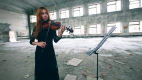 Juegos profesionales del violinista por las notas en un cuarto grande del edificio abandonado almacen de metraje de vídeo
