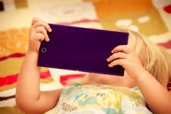 juegos rubios de la muchacha con el primer del smartphone Fotografía de archivo libre de regalías