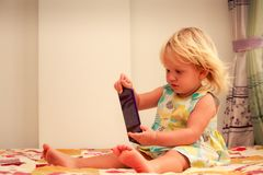 juegos rubios de la muchacha con el primer del smartphone Imagenes de archivo