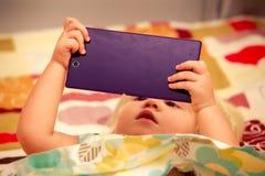 juegos rubios de la muchacha con el primer del smartphone Foto de archivo libre de regalías