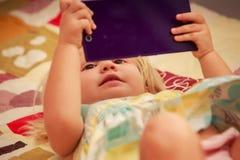 juegos rubios de la muchacha con smartphone Imagen de archivo libre de regalías