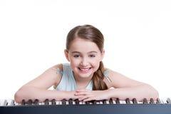 Juegos sonrientes de la muchacha en el piano eléctrico. Imágenes de archivo libres de regalías