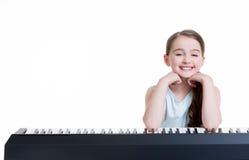 Juegos sonrientes de la muchacha en el piano eléctrico. Fotografía de archivo