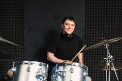 Juegos sonrientes del batería en sistema del tambor imagen de archivo