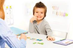 Juegos sonrientes del muchacho que desarrollan el juego con las tarjetas Fotos de archivo libres de regalías