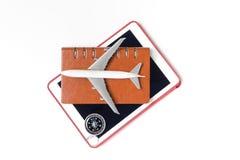 Juegue el avión con el cuaderno en la tableta y el compás aislados en blanco Imagenes de archivo