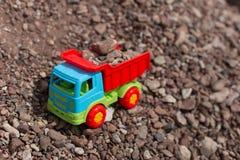 Juegue el camión contra un contexto de la arena y de piedras Imágenes de archivo libres de regalías