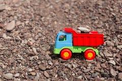 Juegue el camión contra un contexto de la arena y de piedras Fotos de archivo libres de regalías