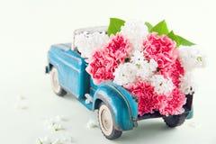 Juegue el camión que lleva las flores rosadas del clavel y de las lilas imagen de archivo libre de regalías