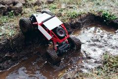 Juegue el coche del rc que sube del charco del fango Fotografía de archivo libre de regalías