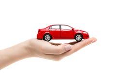 Juegue el coche en la mano femenina en el fondo blanco Imagen de archivo