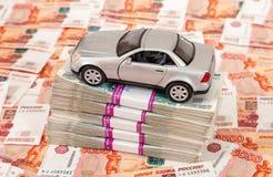 Juegue el coche en la pila de cuentas de las rublos Foto de archivo libre de regalías