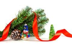 Juegue el muñeco de nieve bajo rama de un árbol de navidad artificial con el cono Imagen de archivo