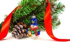 Juegue el muñeco de nieve bajo rama de un árbol de navidad artificial con el cono Imágenes de archivo libres de regalías