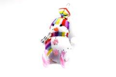 Juegue el muñeco de nieve en los esquís de un caramelo rosado rayado en un fondo blanco Recuerdo de la Navidad Foto de archivo
