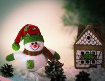 Juegue el muñeco de nieve y una casa de pan de jengibre en un fondo ligero Fotografía de archivo libre de regalías