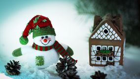 Juegue el muñeco de nieve y una casa de pan de jengibre en un fondo ligero Foto de archivo libre de regalías